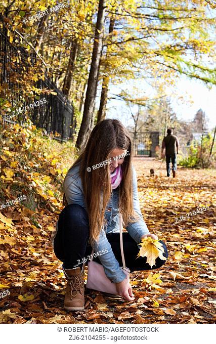 Girl collecting fallen leaves. Wolfgang lake, Austria