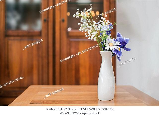 flowers in white vase in the living room on a table close-up vintage design