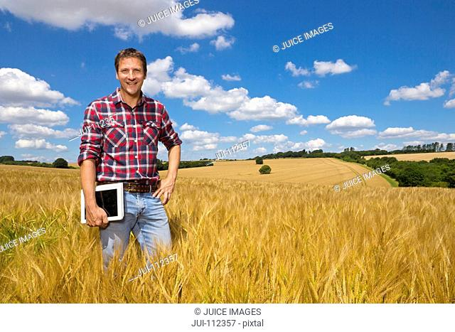 Portrait smiling farmer with digital tablet in sunny rural barley crop field in summer