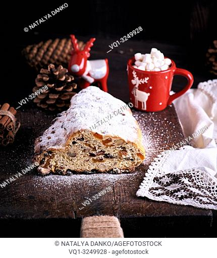 traditional European cake Stollen with nuts and candied fruit dusted with icing sugar