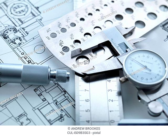 Engineering Measurement, Dial calipers sitting on a steel rule with micrometer and engineering drawings