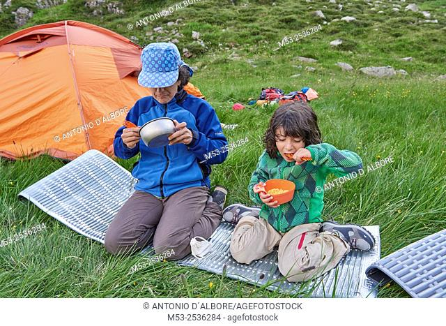 A mother with her 5 years old daughter have a meal nearby their camp site