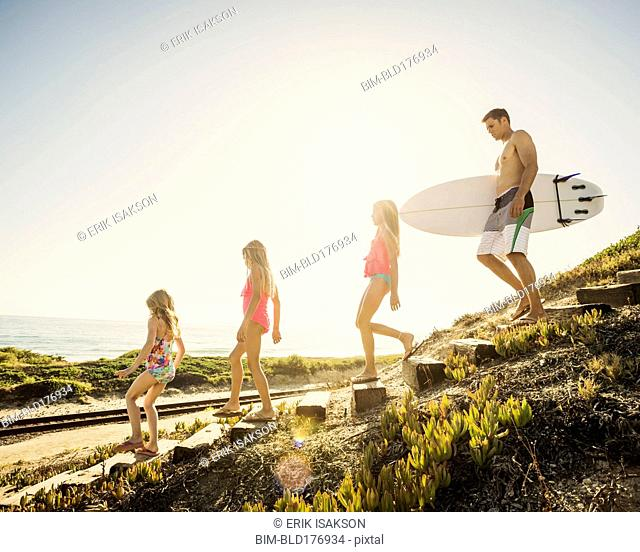 Caucasian father and daughters walking on beach