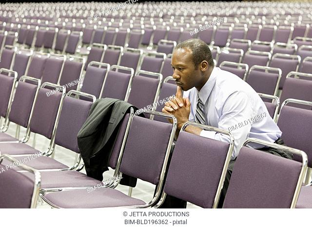 Black businessman waiting in empty conference center