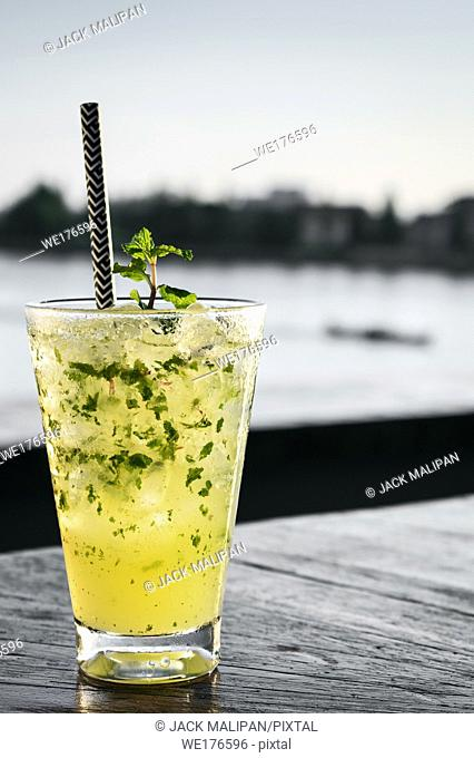 orange mojito summer cocktail drink on outdoor riverside bar tabe
