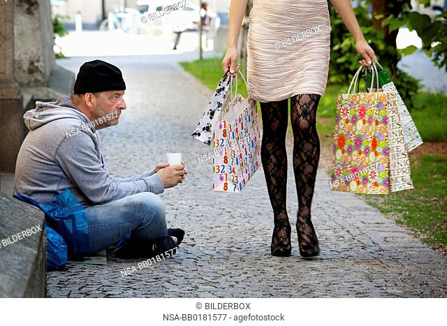 A beggar and a rich woman with shopping bags while shopping