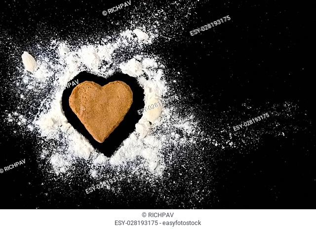 Gingerbread heart with almond and flour isolated on black background