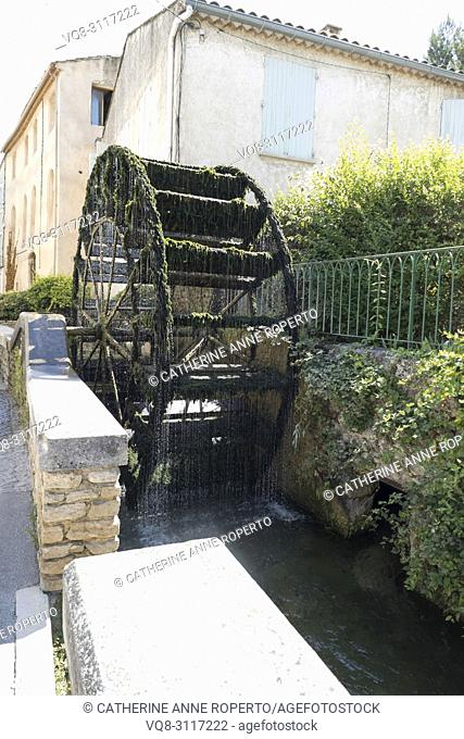 Moss covered waterwheel with shimmering beads of clear water cascading into the transparent waters of the river Sorgue in L'Isle-sur-la-Sorgue, Provence, France