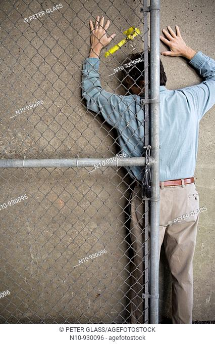 Man behind a chain-link fence door