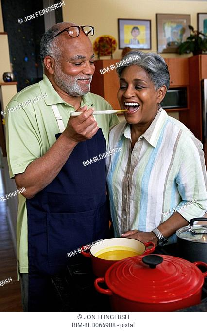 African woman tasting husbandÕs cooking