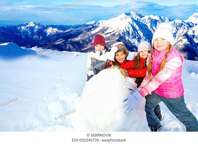 Four friends, tree girls and one boy rolling the huge snowball on mountain peaks