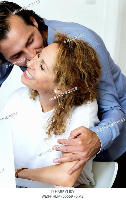 Man kissing his laughing wife