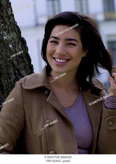 Smiling dark-haired woman outside