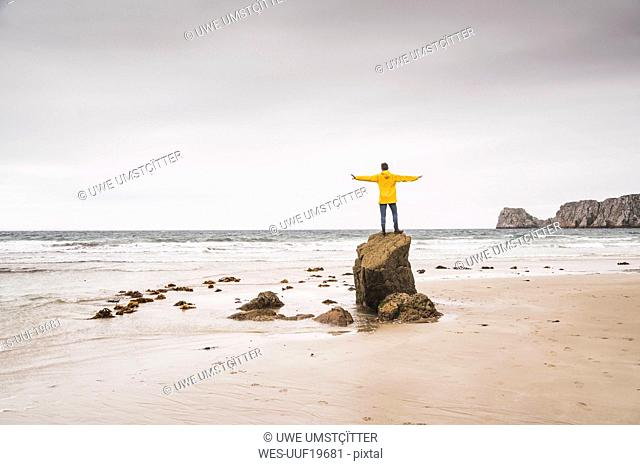 Young man wearing yellow rain jacket at the beach and standing on rock, Bretagne, France