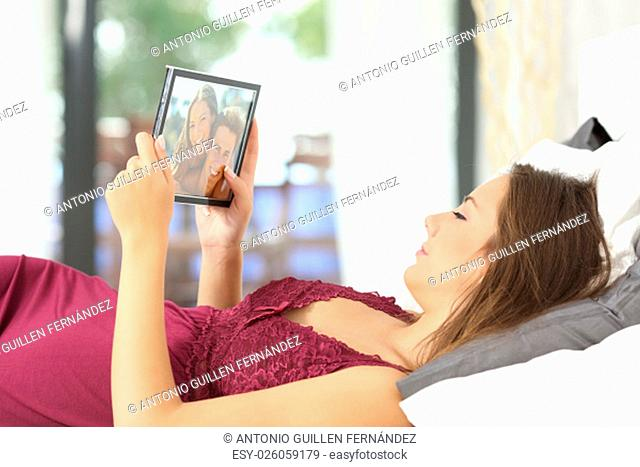Longing woman looking a picture of her boyfriend in a frame on the bed at home