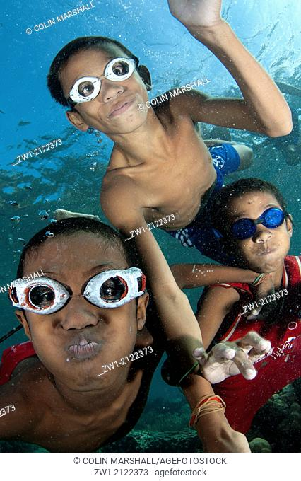 Trio of boys with goggles playing in the water at Pura Island near Alor in eastern Indonesia