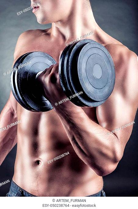 Young muscular man with dumbbells on a black background