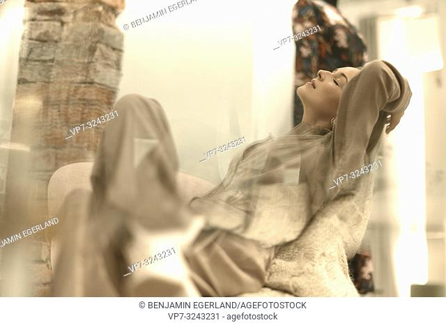 desire for fashion, fashionable woman relaxing in armchair, closed eyes, passion, in Munich, Germany