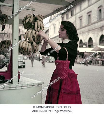 A girl analyzes some bananas at a fruit stall before buying them. Umbria (Italy), June 1955