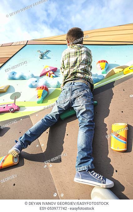 Child climb a climbing wall. Playground