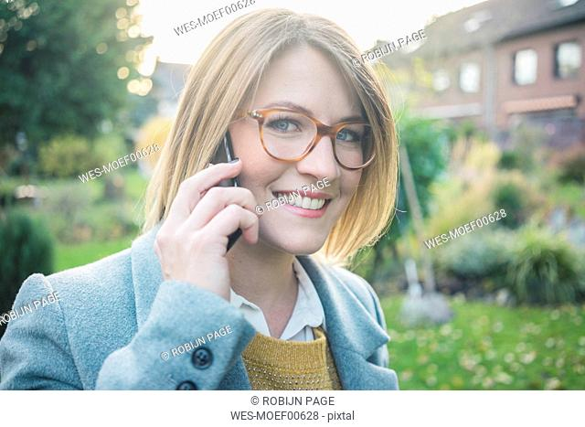 Portrait of smiling woman on cell phone in garden