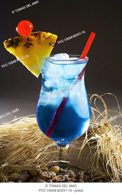 A Blue Hawaii garnished with pinapple and a cherry