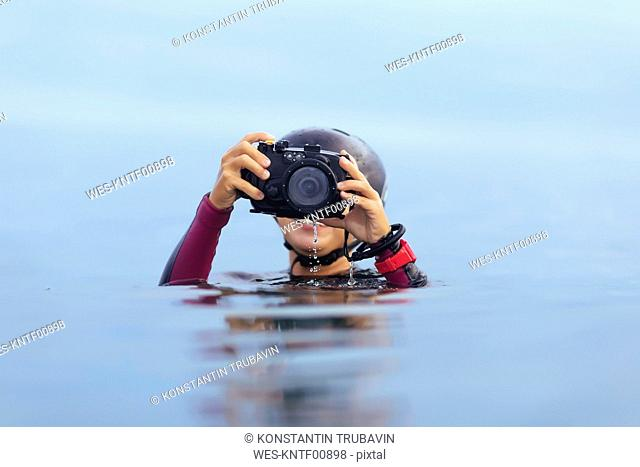 Smiling woman holding underwater camera in the ocean