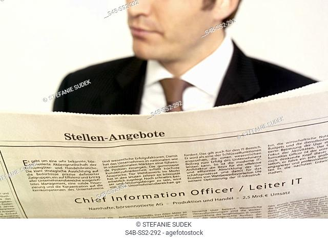Close-up of a business man holding a newspaper