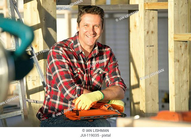 Portrait of carpenter holding nailgun on indoor building construction site and smiling at camera