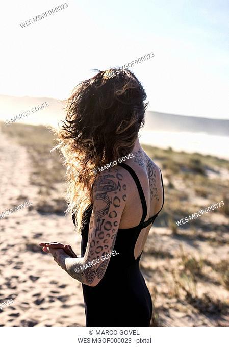 Spain, Asturias, Aviles, woman practicing yoga on the beach
