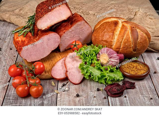 Ham, bread and vegetables on a wooden desk