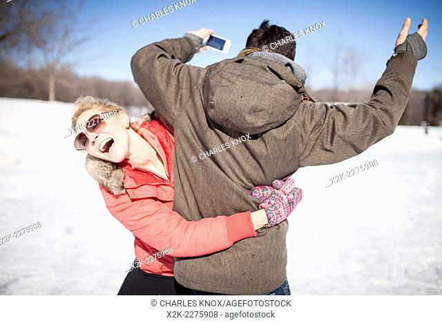 Young attractive couple play fighting while ice skating
