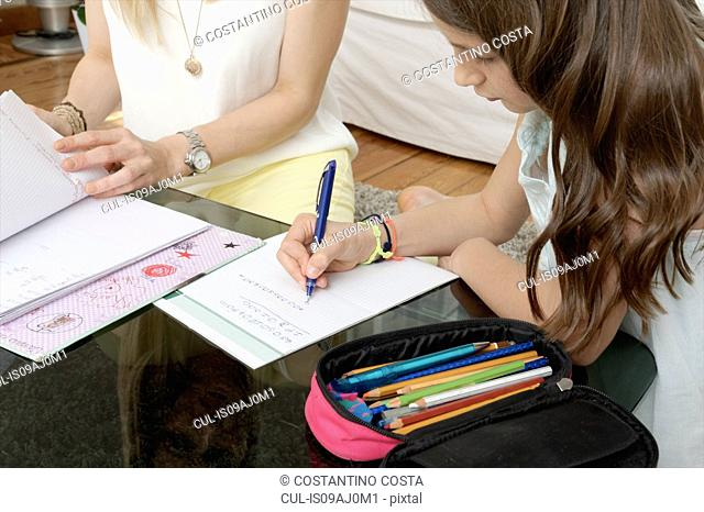 Close up of mother and daughter writing on notepad