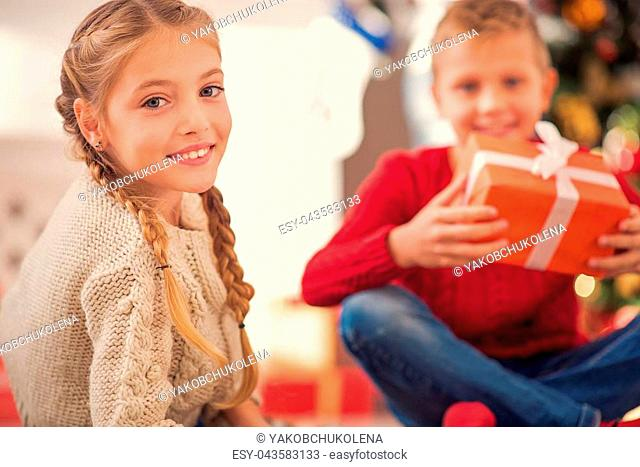 Cute kids are sitting near Christmas tree and smiling. Girl is looking at camera with happiness. Boy is holding present