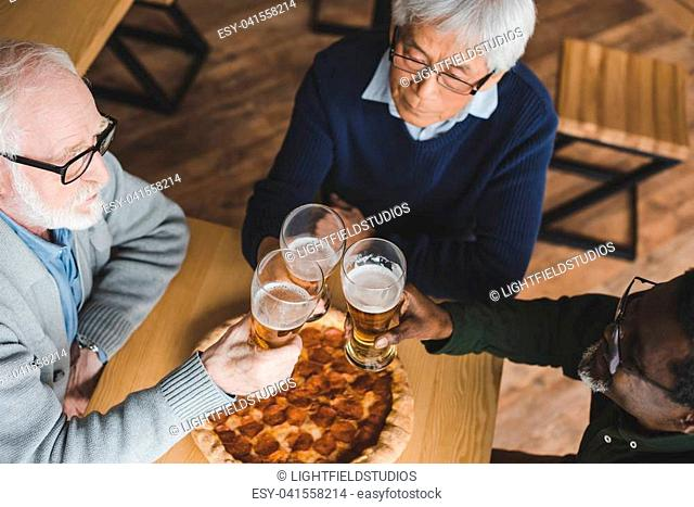 high angle view of group of senior friends clinking glasses of beer in bar with pizza on table