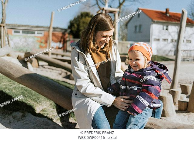 Happy mother with little daughter on a playground