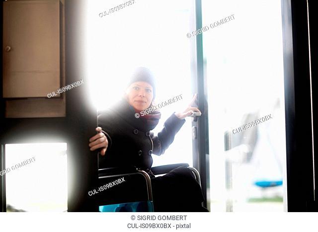 Woman in wheelchair entering building