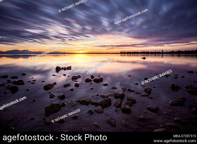 Cloud reflection in the Chiemsee beach with stones and colorful clouds, Seebruck, Bavaria, Germany