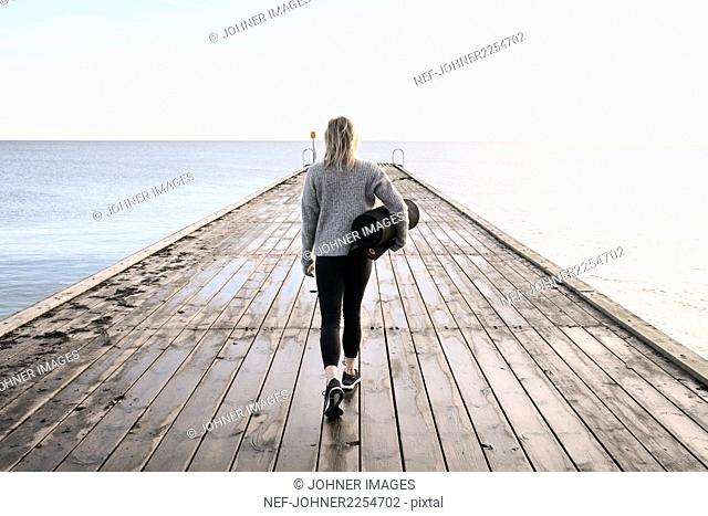 Woman holding exercise mat, walking on pier
