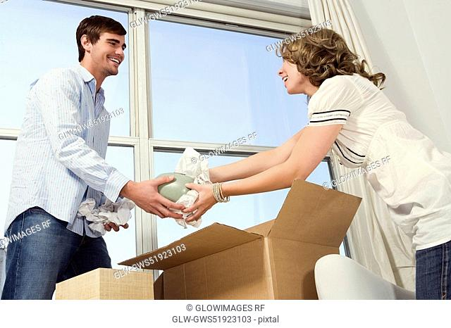 Young couple unpacking a cardboard box and smiling