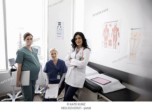 Portrait confident female doctor and nurses in medical examination room