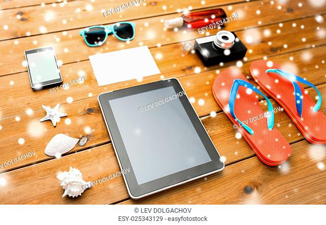 vacation, tourism, winter holidays, technology and travel concept - tablet pc computer and beach stuff over snow