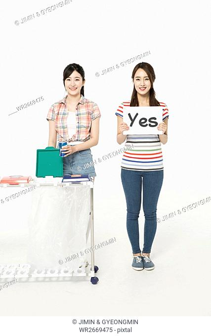 Young smiling women practicing separate garbage collection