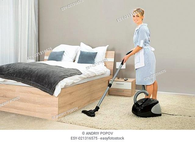 Female Housekeeper Cleaning Rug With Vacuum Cleaner In Hotel Room