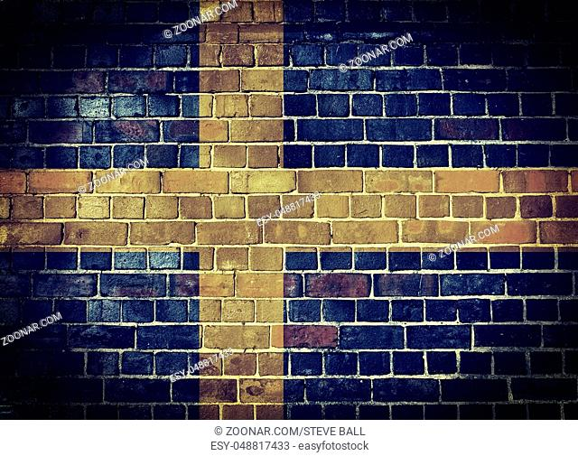 Faded Swedish flag on an old brick wall background with a dark vignette