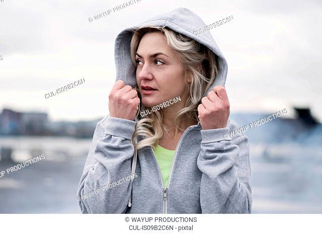 Female runner putting up hoody on rainy dockside