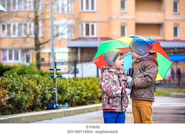 Two little boys, squat on a puddle, with little umbrellas. friendship communication concept