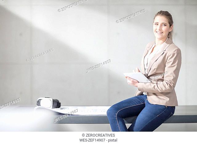 Portrait of smiling young woman with blueprint, VR glasses and tablet in office