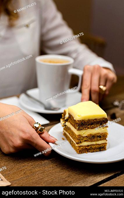 Businesswoman having coffee and carrot cake at table