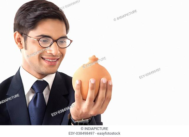 Close-up of young professional man looking at clay saving pot in hand against white background